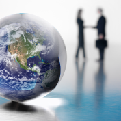 A globe with two business people in the background