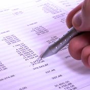 Someone using a pen to go through a set of financial figures